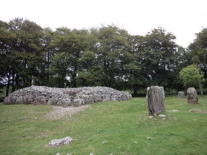 Clava Cairn. It would have had a stone vaulted ceiling, with the entrance passage only tall enough to crawl through. Earth covering the whole thing.