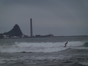 A surfer on Fitzroy Beach. The old New Plymouth Power station sits on the coast (funnel). Paritutu rock is behind - this is the lava plug of an ancient volcano, since eroded away.